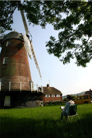 An artist enjoys the tranquility of Polegate Windmill on a fine day